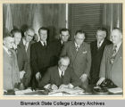 Governor Norman Brunsdale signing land bill for Bismarck Junior College campus on capitol grounds,...