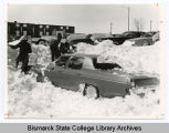Students work to remove vehicle from snow bank at Bismarck Junior College, Bismarck, N.D.