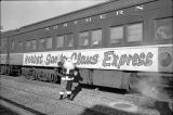 Santa Claus standing by the Herbst Santa Claus Express Train, Fargo, N.D.