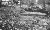 Bulldozer and men work clearing 3rd Street N. after 1957 tornado
