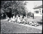 Children on the sidewalk with mini parade floats, N.D.