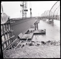 Men and a crane working on a new bridge next to the Lewis and Clark bridge, Williston, N.D.