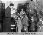 Father Hildebrand distributing Christmas presents