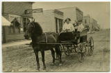 Boys in a horse-drawn buggy near the ND Land and Loan Company and Citizens State Bank, Rugby, N.D.