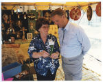 Helen Guilbert showing Governor George Sinner her wheat crafts inside exhibition booth, Bismarck,...