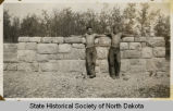 Two Civilian Conservation Corps members at a stone wall, International Peace Garden