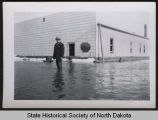 Red Horse Johnson standing in flood water outside locker plant, Pembina, N.D.