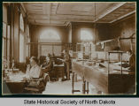 Unknown woman, Leonard Bell, Dick Peuwarden, and an unknown man in First National Bank, Bismarck,...