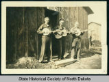 Three musicians standing in front of barracks 8, Civilian Conservation Corps camp 2772, near...