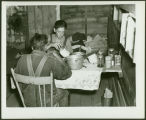 Young men eating inside a shack, Fargo, N.D.