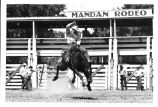 George Mills riding a bronco at Mandan Rodeo