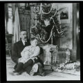 William C. and Elwell Treumann sitting on floor next to Christmas tree, Grafton, N.D.