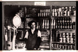 Adolph Garness behind counter in his father Ole Garness' general store, Powers Lake, N.D.