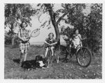 Louise Aandahl with tennis racket and Marilyn and Margaret Aandahl on bicycles on Aandahl farm,...