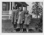 Louise, Margaret and Marilyn Aandahl, wearing dress coats, standing by house on Aandahl farm, Litchville,