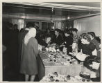 People being served food in basement
