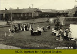 Groups of women and children gathered around tables on lawn by railroad station, Marmarth, N.D.