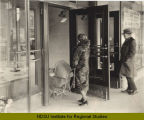 Women with baby carriage entering Herbst Department Store, Fargo, N.D.