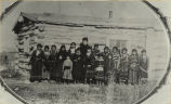Mrs. Van Solen and her class in front of the first school building