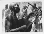 Nuba tribesman playing musical instrument