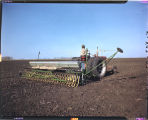 John Scott, Gilby, N.D. seeding crop in spring of year, tractor & drill with fertilizer...