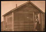 Grace Jacobsen standing at door to her homestead shack
