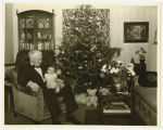 Christmas tree in living room with elderly man holding an infant