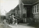 Mildred Sheldon and young girl beside Phi Omega Pi Sorority House, Fargo, N.D.