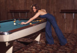 Female model for Herbst Department Store playing pool, Fargo, N.D.